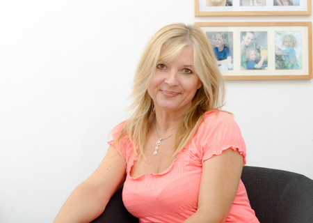 Portrait of blond mature woman relaxing in sofa Stockfoto