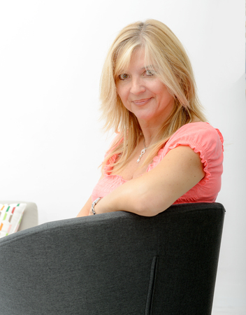 cocooning: Portrait of blond mature woman relaxing in armchair