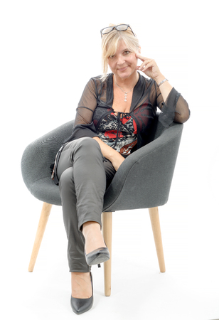 Portrait of blond mature woman relaxing in armchair