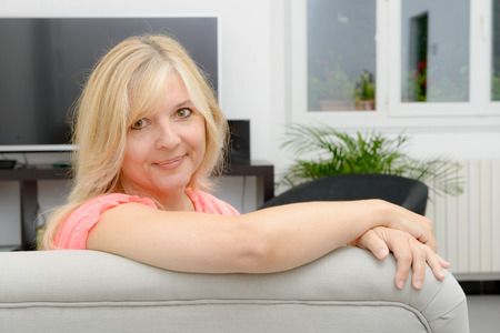 cocooning: Portrait of blond mature woman relaxing in sofa Stock Photo