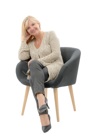 a portrait of blond mature woman relaxing in armchair Stock Photo