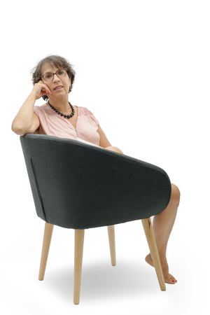 a portrait of brunette mature woman relaxing in armchair