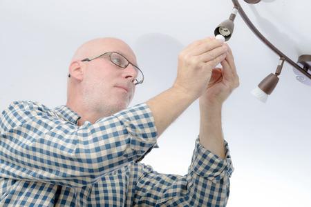 replacing: a mature man replacing the light bulb at home