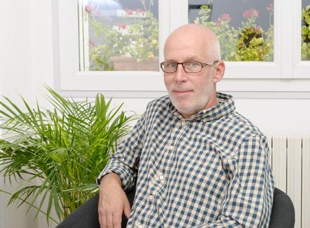 portrait of a smiling mature man with glasses at home Foto de archivo