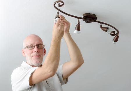 a mature man replacing the light bulb at home