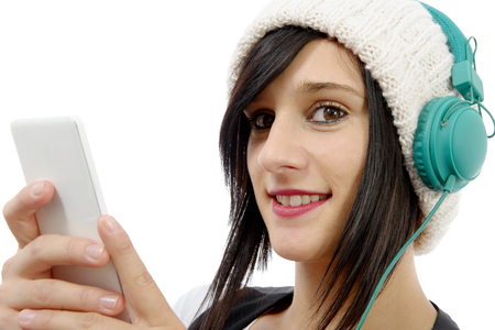 young brunette listening to music with headphones and  phone on white
