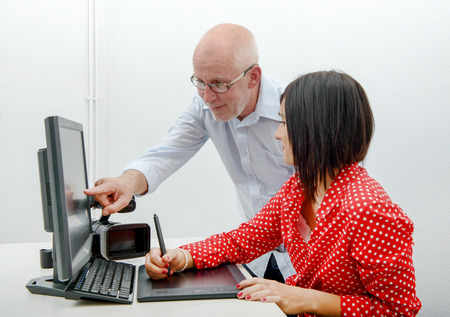 stylus: Young female designer and mature man using graphics tablet while working with computer Stock Photo