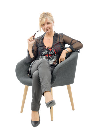 cocooning: Portrait of beautiful mature  blond woman sitting on armchair Stock Photo