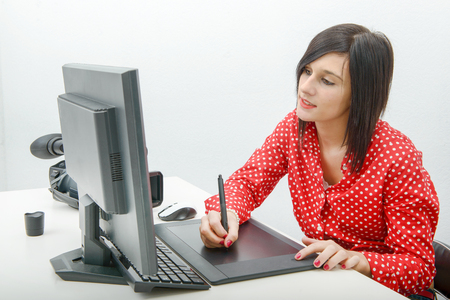 Young brunette female designer using graphics tablet while working with computer Stock Photo