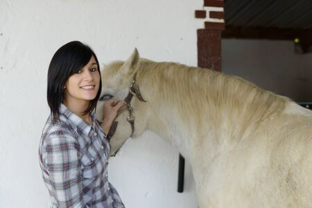stale: Beautiful young brunette girl and white horse in the stale
