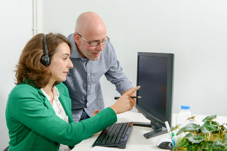 beautiful young secretary and his boss in the office Stock Photo