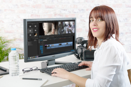 young smiling woman designer using computer for video editing Foto de archivo