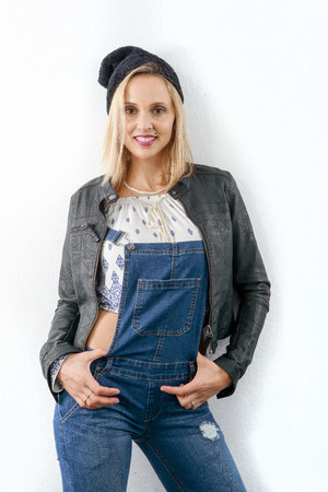 fashion young blonde woman with jeans overalls and black jacket