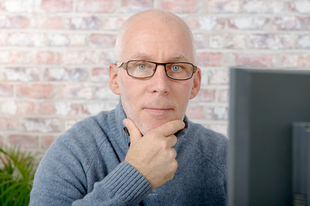 Portrait of a handsome mature man using computer at office Stock Photo