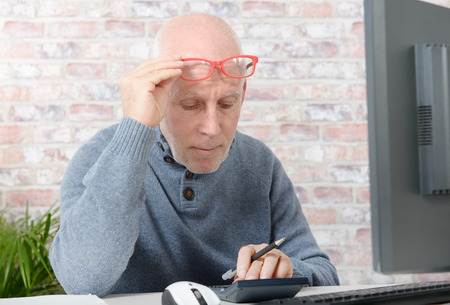 shortsighted: mature businessman having eyesight problems, he is using calculator Stock Photo