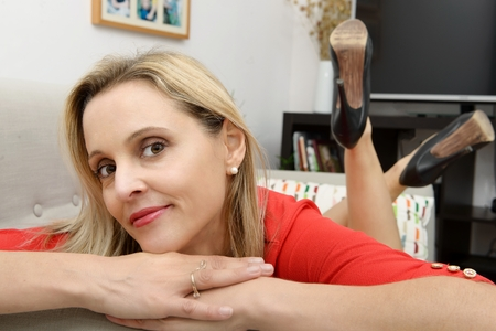 woman on couch: Beautiful young blonde woman lying on the couch at home