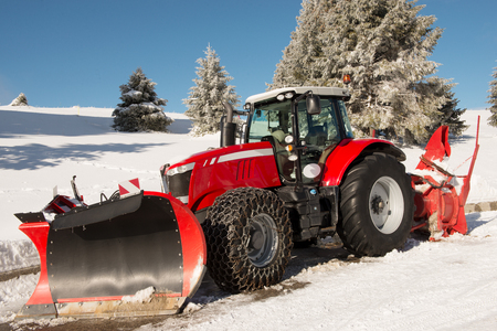 plowing: Red tractor for snow removal in french Alps