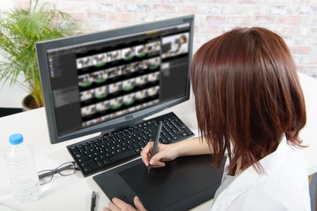 비디오 편집을 위해 컴퓨터를 사용하는 젊은 여성 디자이너