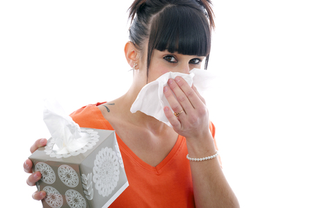 hankie: sick young brunette girl blowing her nose isolated on white background Stock Photo