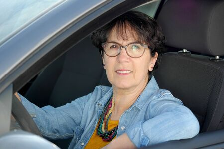 smiling brunette mature woman driving car
