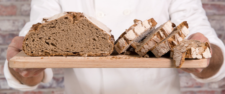 a baker hands with fresh bread on wood table
