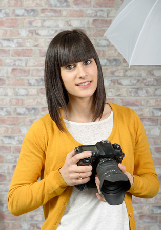 Attractive smiling brunette woman with photo camera