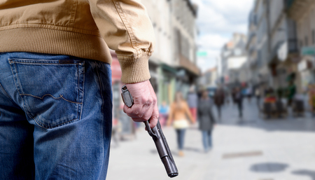 killer attacking with  gun on public place Stock Photo