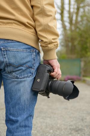 man photographer holding his photo camera, outdoor  Stock Photo