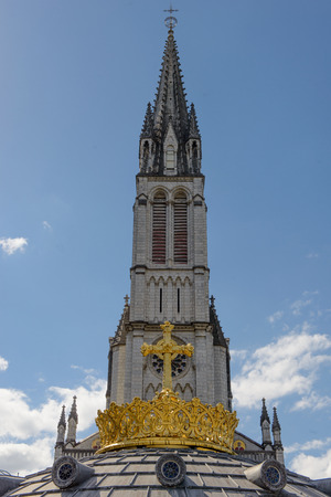 The Upper Basilica with gilded crown ad cross in Lourdes, France Stock Photo