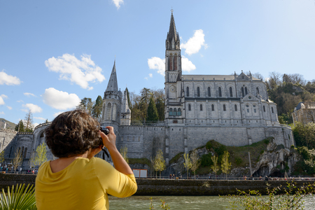 brunette woman photographs the cathedral in Lourdes, France Stock Photo