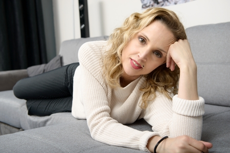 an attractive blond woman relaxing on the sofa in her home Stock Photo