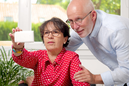 a cheerful senior couple taking selfie at home Stock Photo