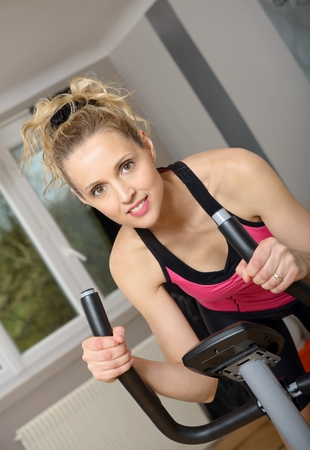 Fit blonde woman on exercise bike at home Stock Photo