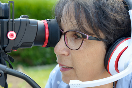 A mature woman with headphones, using a camera dslr