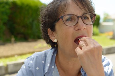 Portrait of a mature brunette woman with eyeglasses in the garden Stock Photo