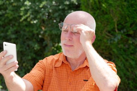 中年の男性彼のスマート フォンで読むための彼の視力に問題があります。 写真素材