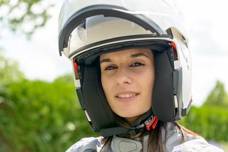 Una chica con hermosos ojos y una cara feliz en casco blanco con una visera abierta