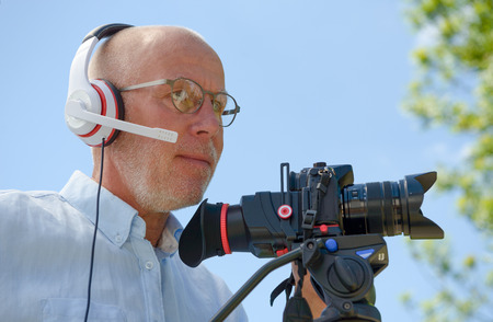 taking video: A mature man with headphones, using a camera dslr