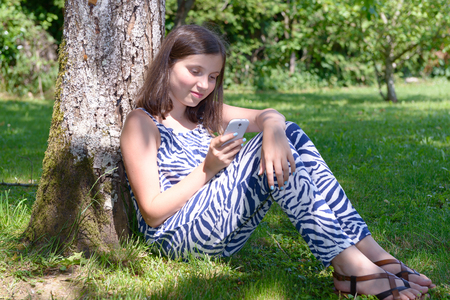 niños platicando: pretty pre teenager girl texting on mobile phone Foto de archivo