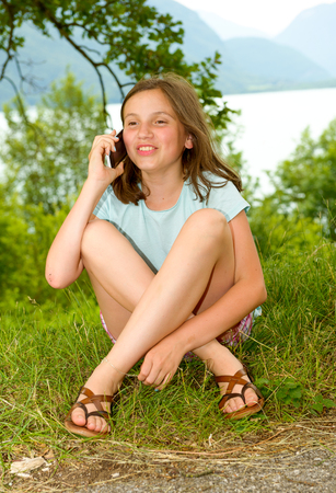 a smiling pre teenager girl calling on smartphone, outdoor