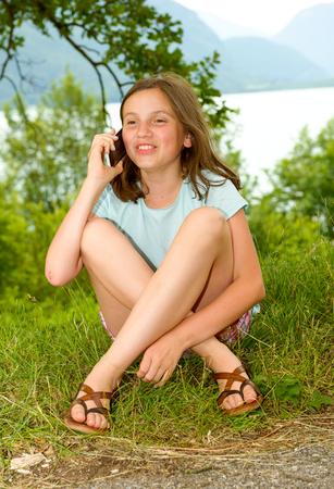 Een lachende pre tiener meisje aanroepen smartphone, buiten