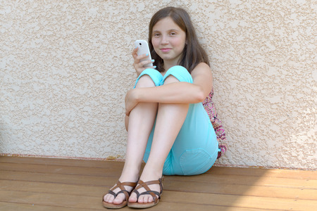 pretty pre teenager girl texting on mobile phone Banco de Imagens