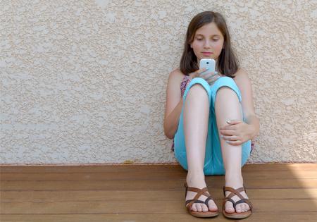 Pretty Pre Teenager Girl texting sur téléphone portable Banque d'images
