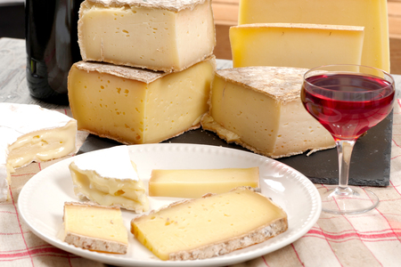 tabla de quesos: Different french cheeses with a glass of red wine Foto de archivo