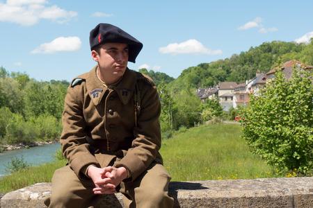 Een Franse soldaat in de uniform van 1940, buiten zitten