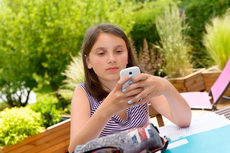 niños platicando: Chica bastante pre adolescente de mensajes de texto en el teléfono móvil