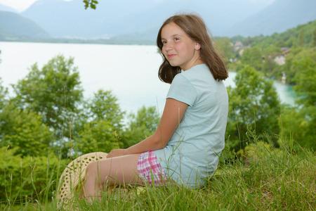 Une jolie pré-adolescente assise dans l'herbe Banque d'images - 82817446