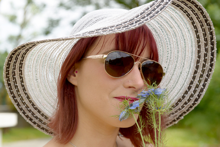 chic: portrait of pretty girl wearing hat and sunglasses. She smelling  flowers