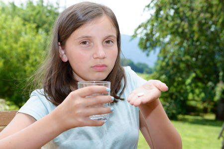 cute girl child taking pill with glass of water Foto de archivo