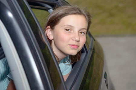 comfortable: young teenage girl sitting in a car